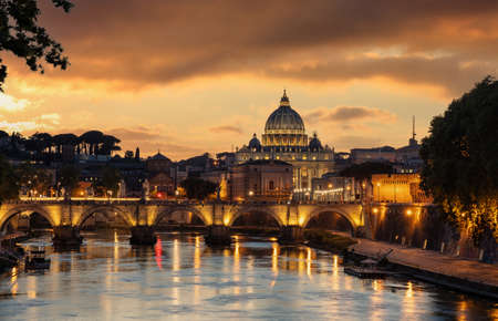 Rome Italy. Saint Peter Basilica in the Vatican over illuminated Sant Angelo bridge and Tiber river night view, orange color sky after sunset Stock Photo