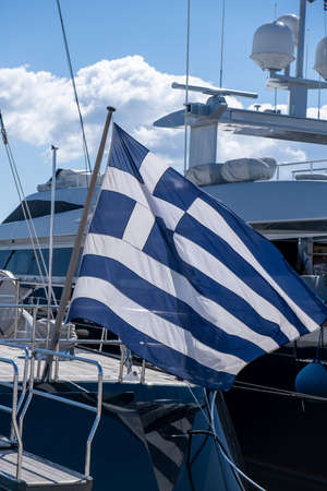 Greek flag on a luxury boat anchored in a marina in Greece. Blue white color flag waving on yacht stern. Blue sky background, close up view.