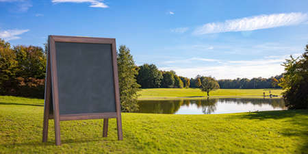 Chalkboard at park next to lake summertime. Wooden frame blackboard blank for advertise. Outdoors standing billboard, promotion, blue sky trees background. Copyspace, banner, template. 3d illustration Reklamní fotografie