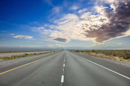 Highway in a sunny spring day, countryside USA. Empty national road going straight, crossing American desert, Blue cloudy sky background