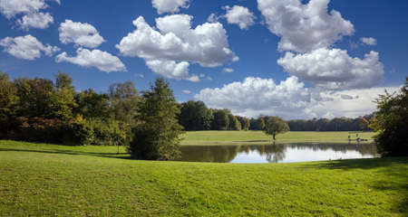 Grass field, trees and a small pond, blue cloudy sky, sunny day. City park, Munich, Germany. Reklamní fotografie