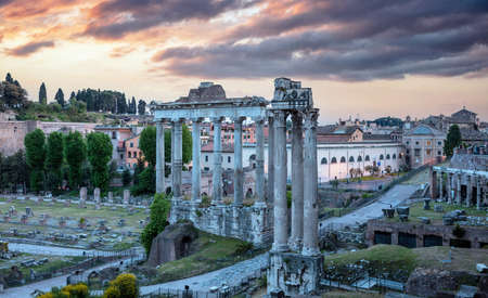 Roman Forum at sunrise in Rome, Italy. Roma top landmark and tourists attraction. Ruins of the ancient forum at Palatino hill, Scenic urban landscape in the morning, cloudy sky.