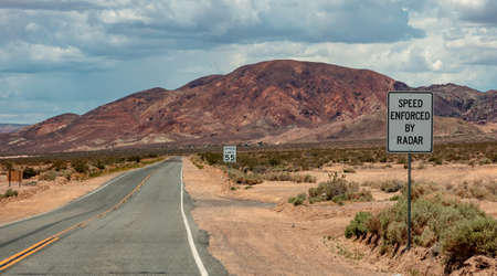 Speed limit 55 MPH. Speed enforced by radar. Warning road signs text in a desert highway. Nevada, USA, Empty scenic asphalt road, cloudy sky background Reklamní fotografie