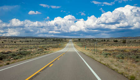 Highway in a sunny spring day, countryside USA. Empty national road with ups and downs, passing through American desert, Blue cloudy sky background Reklamní fotografie