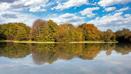 City park, autumn, Munich, Germany. Trees fall foliage cloudy blue sky, sunny day. Reflections in a pond, Reklamní fotografie