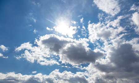 Sunbeams and fluffy cumulus clouds on blue sky background, sunny day. Sun shining and cloudscape white and grey color,
