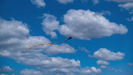 Festival concept. Traditional kite with colorful tail free on cloudy blue sky background. One kite toy flight high on air with wind help, make kids happy, entertainment, joy. Under view, banner. Reklamní fotografie