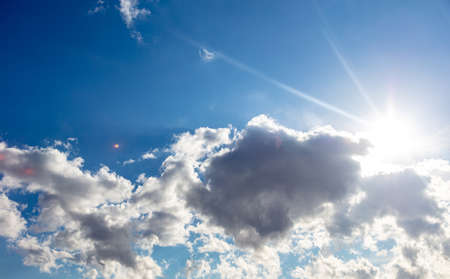 Sun shining and cloudscape white and grey color, on blue sky background, sunny spring day. Sunbeams and fluffy cumulus clouds