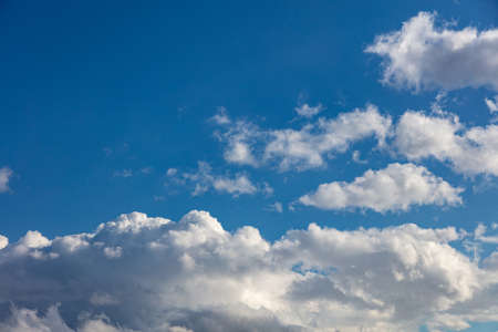 Cloudscape on blue sky background. Fluffy cumulus clouds white and grey color and empty sky, copy space, card template.