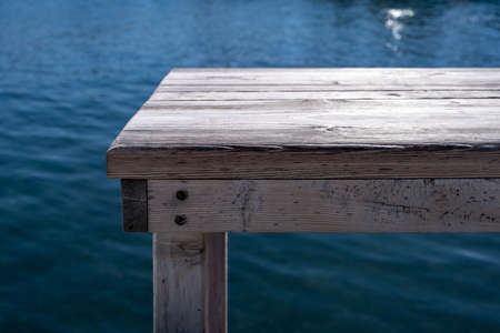 Old empty grey wooden bench, pier over blur blue sea background. Waterfront fish tavern table, wood planks, platform for relaxation, sunny summer day. Vacation, travel, tourism at nature. Reklamní fotografie