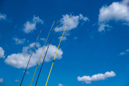 Fishery concept. Fishing rods in row ready to catch fishes. Angling at sea with fishing poles at seaside. Blue sky background, space. Leisure at nature, activity, hobby, sport, recreation at vacation.