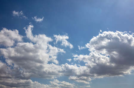 Fluffy cumulus clouds on blue sky background. Cloudscape white and grey color and empty sky, copy space, card template.