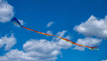 Traditional kite with colorful tail free on cloudy blue sky background, sunny day. Kids and adults leisure activity, freedom happiness concept.