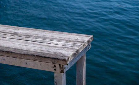 Waterfront empty table, old wooden bench for product presentation, blue sea background, copy space advertise template. Sunny day, summer holidays, travel and tourism to greek islands