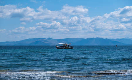 Traditional fishing boat sailing in rippled sea background. Blue and white trawler in the middle of Aegean sea a cloudy day. Fishery at nature, job, sport, hobby, summer holidays in Greece. Reklamní fotografie