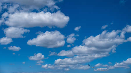 Traditional kite with colorful tail free on cloudy blue sky background. Fluffy cumulus cloudscape white and grey color