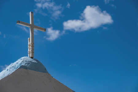 Christianity religion concept. White broken metal rusty old cross tied with rope on Greek island church rooftop. Crucifix Orthodox, Catholic, Protestant symbol. Copy space, empty. Blue sky background.