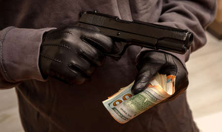 Thief threatens with a pistol for stealing money, closeup view. Armed robbery, man holding a gun and banknotes in gloved hands,