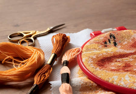 Canvas with embroidered cross pattern tucked into the embroidery frame, colorful floss threads and scissors lying next to it. Cross stitch, hobbies and recreation, do it yourself concept