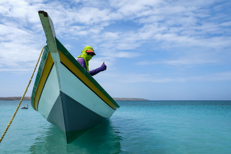 A fishing boat anchored next to the coast of Cuba with a hooded sailor man (Venezuela). Reklamní fotografie