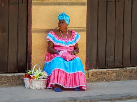 A typical cuban woman with a traditional dress smoking a cigar in a public street (05.15.2016, Havana, Cuba). Editorial