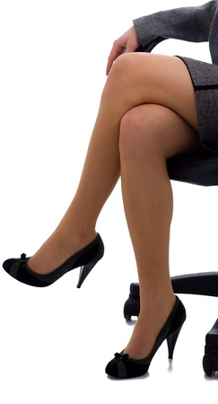 Legs of business woman sitting on a chair photo