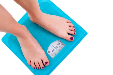 weighing scale: Woman on weight scale on isolated background
