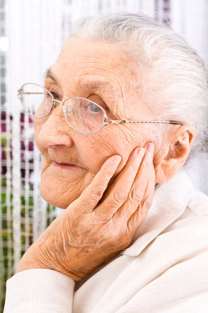 congenial: Old woman at the window, dreaming the past Stock Photo