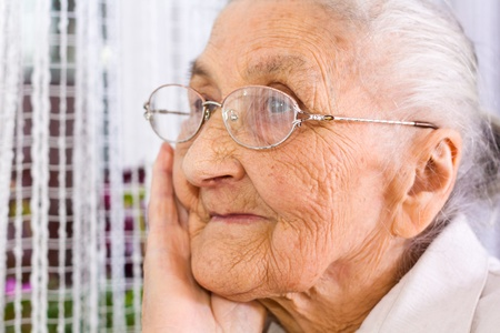 mature old generation: Old woman at the window, dreaming the past Stock Photo