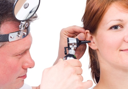 eustachian: Doctor using otoscope to look in a girl