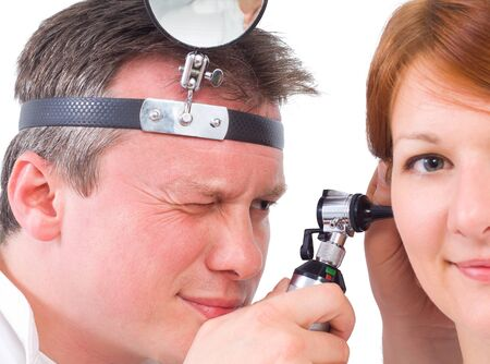 otoscope: Doctor using otoscope to look in a girl