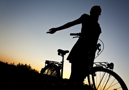 Girl on old bicycle at sunset