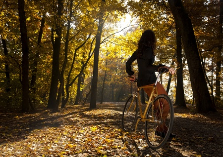 Beautiful girl with bicycle in park Stock Photo