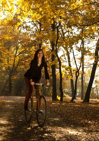 Beautiful girl riding a bike in the park photo
