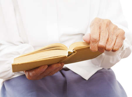 old woman sitting and holding an old book in her hands photo