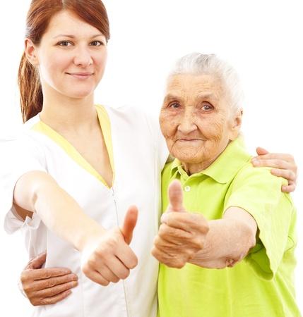 old dame: un giovane medico di sesso femminile e una donna molto vecchia che mostra pollice in alto Archivio Fotografico