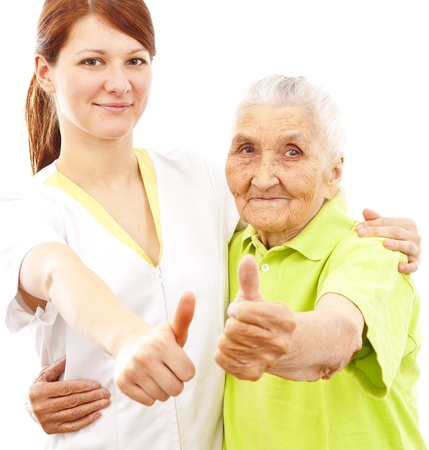 damas antiguas: una joven doctora y una mujer muy vieja que muestra los pulgares para arriba Foto de archivo