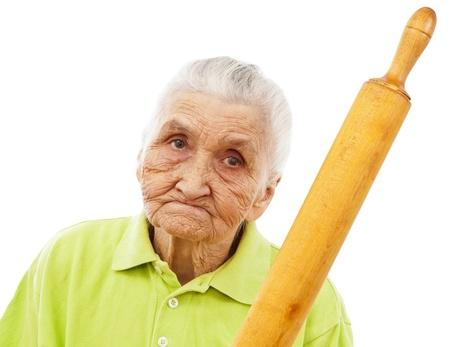 persona enojada: mujer enojada de edad sosteniendo un palo de amasar en la mano Foto de archivo