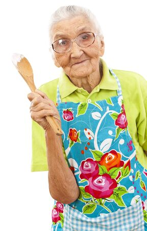 old woman holding a a wooden spoon in her hands  photo