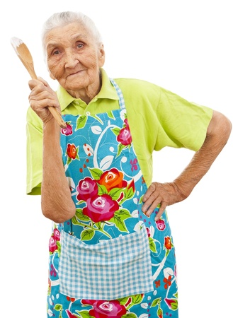 grandmother: old woman holding a a wooden spoon in her hands
