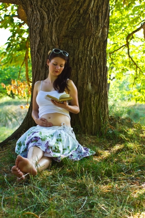Pregnant attractive woman reading in park photo