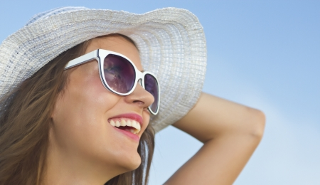 sun protection: beautiful girl with white hat staring at the sun