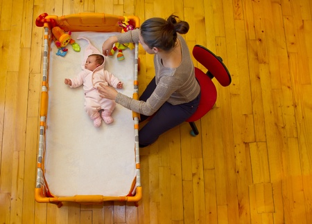 mother preparing to stroke her baby sitting next to it near her bed