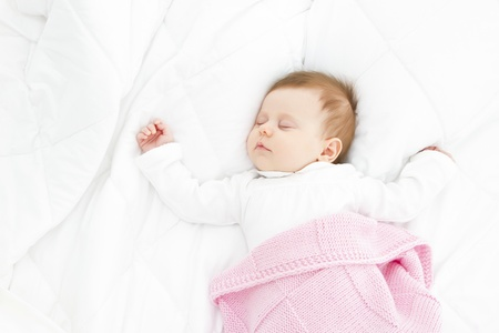adorable baby sleeping in a white bed with a pink blanket