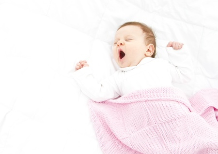 adorable gapy baby ona white bed witha  pink blanket photo