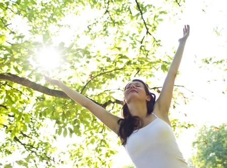 夏にツリーの下で幸せな女
