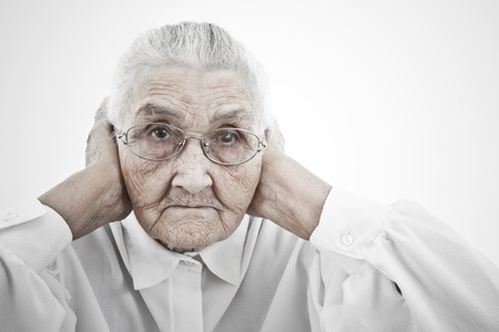 decrepitude: old lady holding her arms to her ears Stock Photo