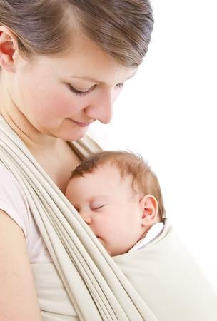 draagdoek: jonge moeder die een pasgeboren kindje sleepimg Stockfoto
