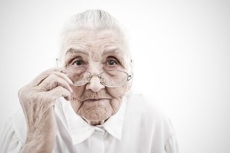 decrepitude: portrait of a very old woman taking off  her glasses