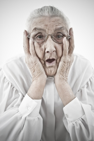 portrait of a surprised old woman who is staring with open mouth Standard-Bild